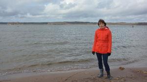 En kvinna i orange jacka och blå byxor står på en strand med vågor som rullar in. Hon heter Anna-Karin Almén.