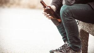 Man sitter på en bänk med en flaska i handen.
