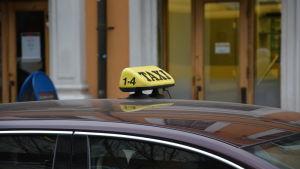 En gul taxiskylt på en bil i centrum av Åbo.