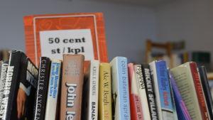 En bild på böcker på en bokhylla och en skylt där det står 50 cent per bok.