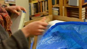 en bild på ett par händer som river sönder en bok.