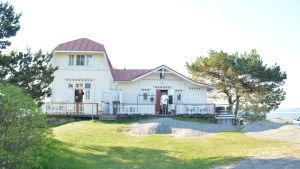 En gammal vit trävilla med rött tak vid havet, framför dörren står en man.
