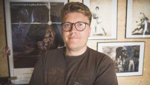 Janne Mällinen poserar framför sina Star Wars-planscher.