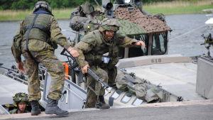 Militärer övar landstigning i terrängsdräkter med vapen. Män tar i land från en båt.