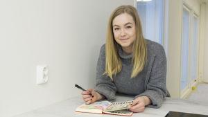 Caroline Eriksson har långt blont hår och en grå tröja. Hon lutar sig över ett bord med ett häfte framför sig. I handen håller hon en penna.