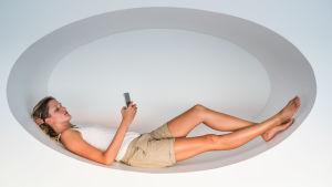 Kvinna tittar på sin mobiltelefon