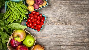 Färska frukter och grönsaker på ett matbord i trä.