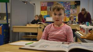 Elev med uppslagen bok framför sig på en pulpet.