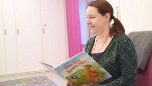 Charlotta Blomqvist sitter med en Mamma Mu-bok i handen.