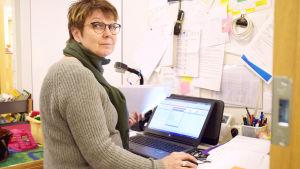 Mervi Harvio-Jokiaho sitter vid ett skrivbord och jobbar med några papper och en dator.
