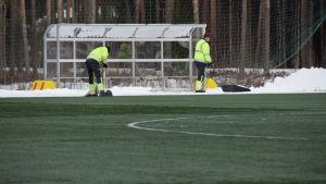 Två män skottar bort litet snö från den annars gröna konstgräsplanen i Karis den 6 mars 2018.