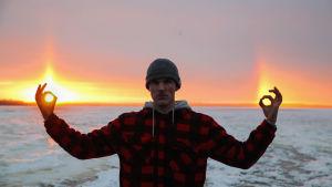 Mies pitää käsiä sivuillaan, sormet ja peukalot yhdessä muodostavat ympyrät, taustalla jäinen meri ja haloilmiö taivaalla, valot osuvat käsiin