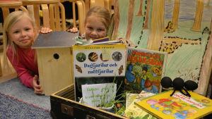 Två flickor tittar fram mellan en kappsäck, några läroböcker och en fågelholk.
