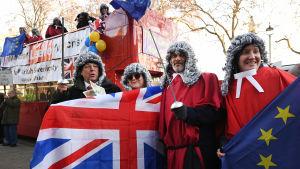 Demonstranter klädda i domarperuker håller upp EU:s och Storbritanniens flagga.