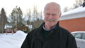 Kaj Mäkelä står utomhus under vintern och tittar in i kameran. Porträtt.