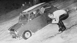 Kalevi Häkkinen åker skidor bredvid en bil.