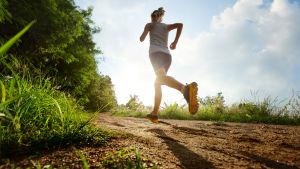 nainen juoksee polulla