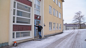 John Rönnholm står vid huvudingången till det nya hotellet. Beige rappat hus i tre våningar med blå dörr.