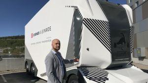 Filip Lilja framför en vit T-pod, ett självkörande fordon.