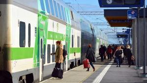 Folk går mot ett VR-tåg av typen Intercity på perrongen vid Bennäs tågstation
