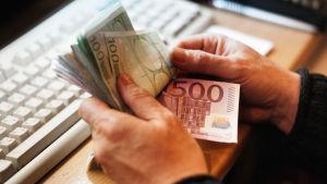 Hand som håller i många eurosedlar.