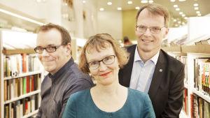 Aapo Reselius, Annvi Gardberg och Anders Gardberg mellan bokshyllor.