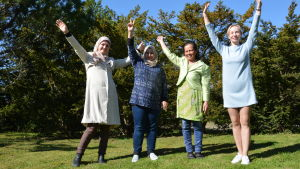 fyra kvinnor av olika nationalitet glada mot grön gräsmatta och blå himmel i solsken
