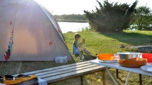 Lapsi lukee kirjaa teltan edessä.