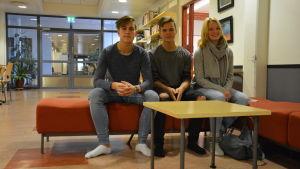 Ungdomar sitter på en bänk i en skolkorridor.