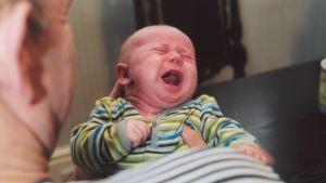 En pappa håller en fyramånaders baby som gråter.