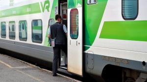 Konduktör stiger ombord på tåg.