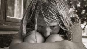 Flicka lutar huvudet i knäna och ser ledsen ut.