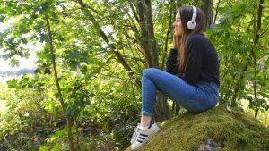 Antonia Holmberg sitter på en sten.