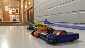 Små leksaksbilar står radade i en kö på ett bord.