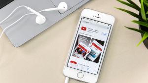 En smarttelefon med hörlurar ligger på ett bord bredvid en bärbar dator.
