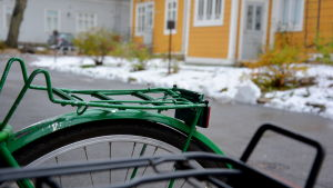 En pakethållare på en cykel i förgrunden med snö och ett hus i bakgrunden.