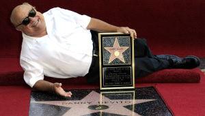 Skådespelaren Danny DeVito poserar bredvid sin stjärna på Hollywoods Walk of Fame.