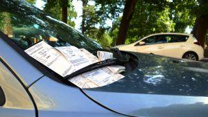 Parkeringsanmärkningar under vindrutetorkarna på en bil.