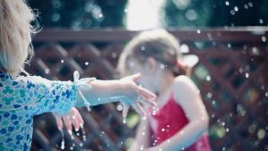Två flickor som leker med vatten