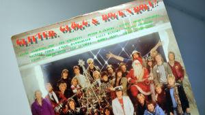 Konvolut till julskivan Glitter, glögg och rock´n´roll med artisterna runt en julgran.