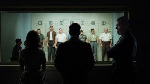 En man och en kvinna står vid ett fönster och ska försöka känna igen misstänkta brottslingar som står uppradade på andra sidan fönstret.