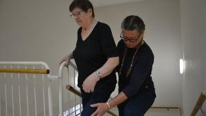 Pirkko Paananen övar sig på att gå i trappan, fysioterapeut Susanne Miikki stöder.