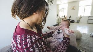 Emilia Jansson håller upp dottern Junia.