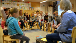 Alla barnen sitter i en ring i klassrummet. Läraren visar en bild.