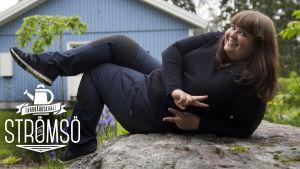 Kristine Vesterlund  poserar liggand epå en stor, grå sten.