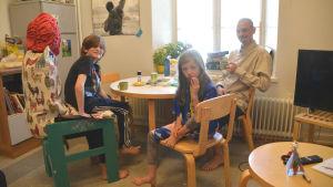 En familj sitter runt ett matbord. Vid första anblicken ser det ut att vara bara en man, en ung flicka och en pojke, men när man tittar närmare ser man att stolen pojken sitter på egentligen är en människa utklädd till stol.