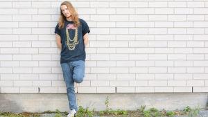 Artisten Cstar, Simon Andersson, står lutad mot en tegelvägg.