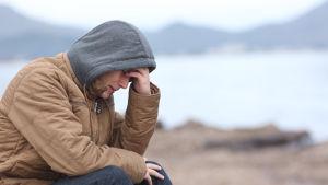 En ung man sitter ledsen på stranden.