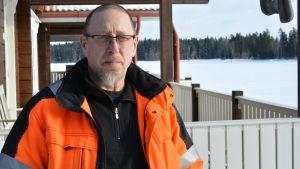 en porträttbild av kenneth höglund. han står utomhus med sin veranda i bakgrunden. han bär glasögon och en orange arbetsjacka.