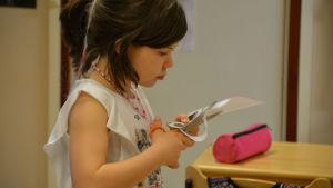 En flicka klipper i ett papper. Hon ser väldigt koncentrerad ut.